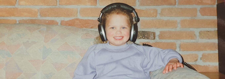 Kleine Lianne den Haan geniet van muziek met een koptelefoon.