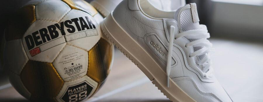 Een voetbal met gympen die er tegenaan leunen